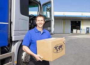Truck driver standing near semi-truck on loading dock holding cardboard box